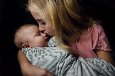 Big sister kissing baby