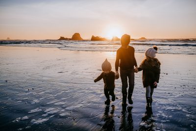 Three siblings holding hands walking on the beach along the Pacific Ocean in Washington.
