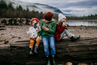 Three children taking a quick snack break during their morning adventures at Rattlesnake Lake in Seattle Washington to enjoy amazing chocolate truffle bars from Seattle Chocolate.