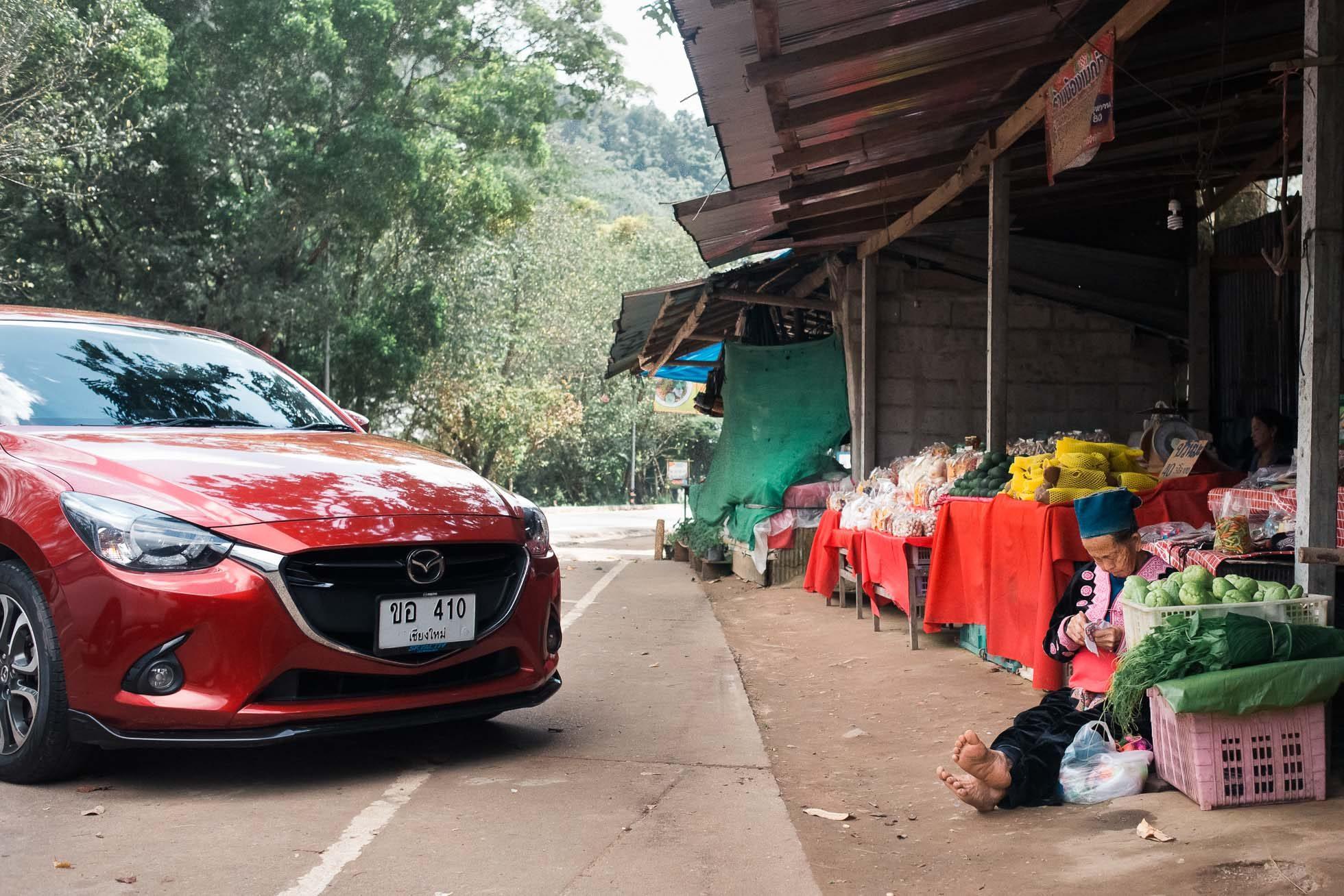 elderly-karen-hill-tribe-woman-handicraft-thailand-market-red-car