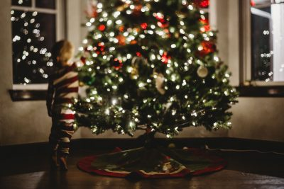 freelensed photo of boy reaching up to christmas tree
