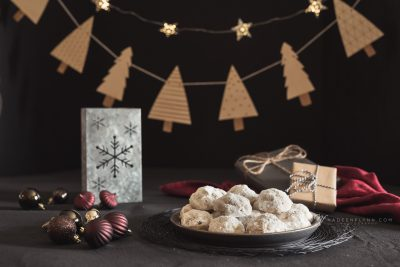 Christmas cookies on a plate with tree garland background
