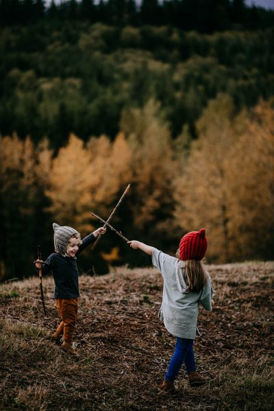 Two siblings sward fighting with adventure sticks east of Seattle, WA.
