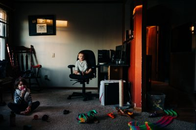late afternoon photo of two kids in a messy livingroom