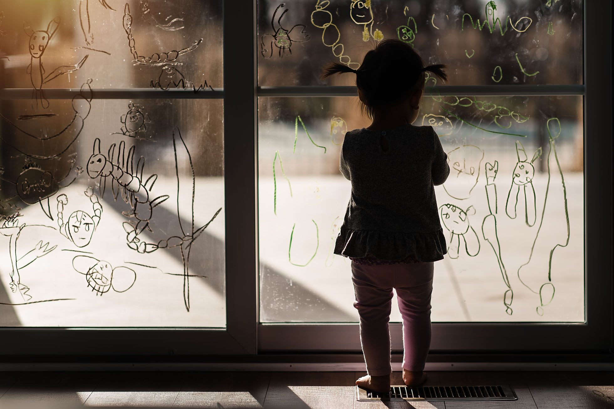 Modern pokemon hieroglyphics on glass door with toddler girl silhouette, Lifestyle photography by Thao Lai of donthaophotography.com