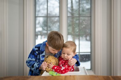 two-brothers-snuggling-together-in-front-of-window-on-snowy-day-1