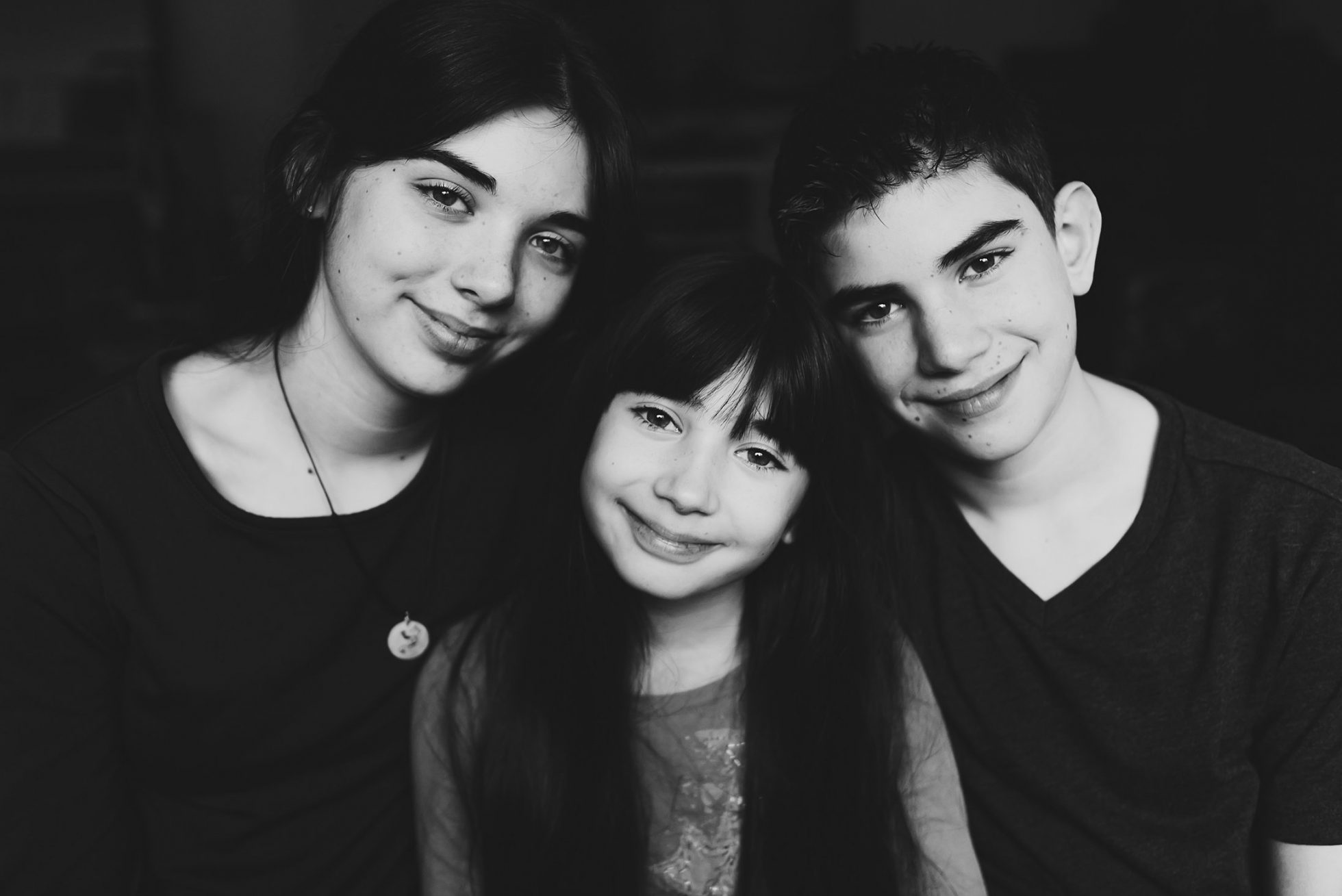 Three children looking at camera in black and white