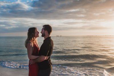 A couple looks happily into each others eyes as the sun sets over the Florida gulf horizon by Saint Pete Beach photographer - Tami Keehn