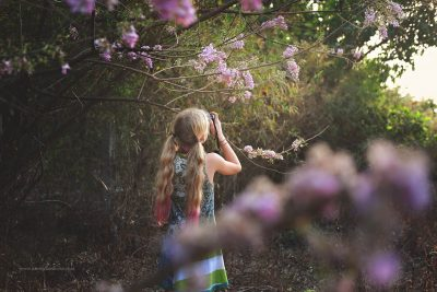 A girl photographs some blossom trees in the countryside, Goa, India
