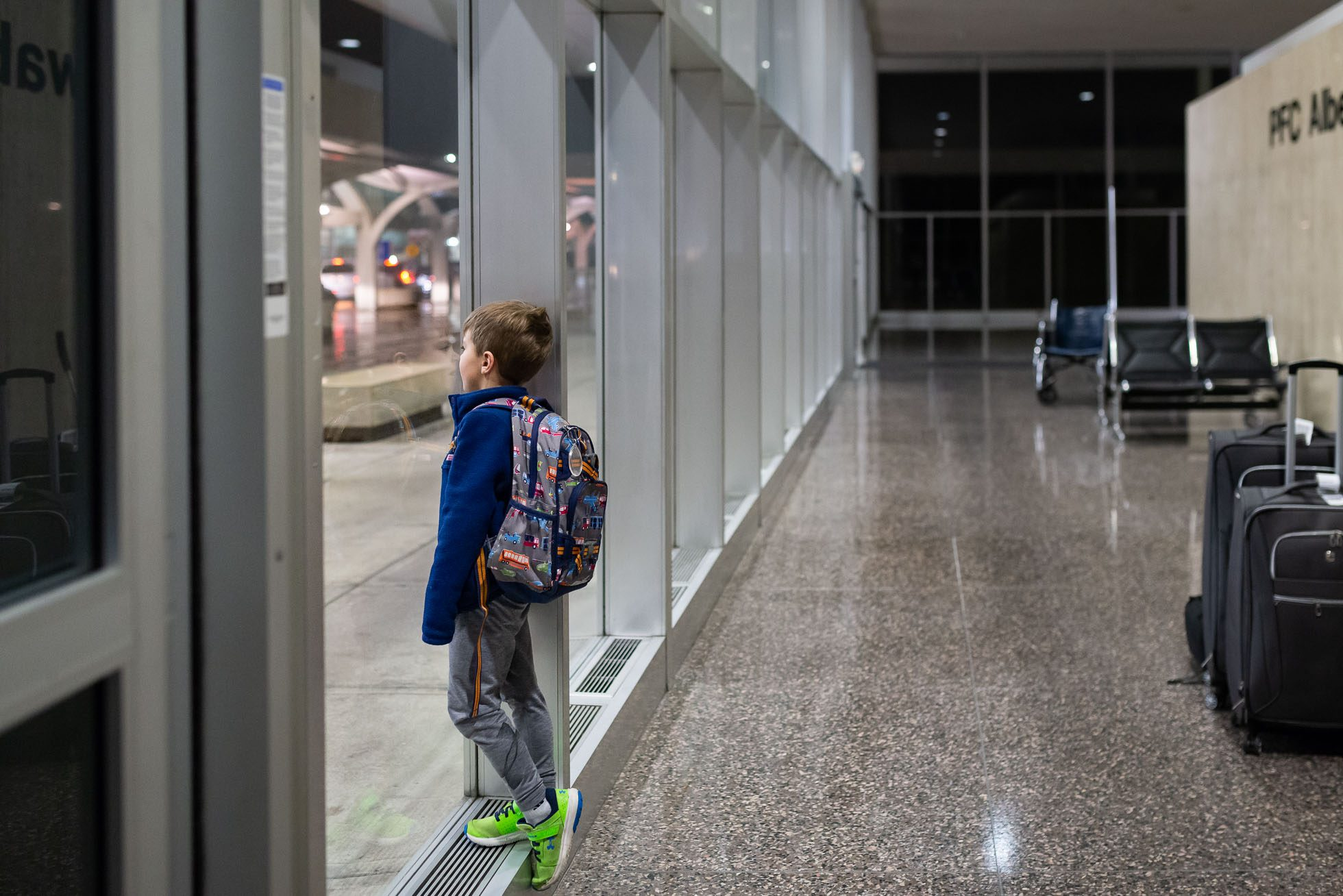 boy-standing-in-front-of-window-at-airport