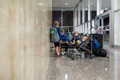 four-boys-sitting-at-aiport-in-front-of-reflective-wall