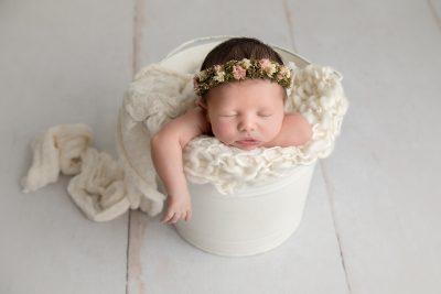 pretty-newborn-baby-girl-wearing-a-floral-crown-asleep-in-a-bucket