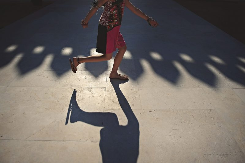 A girl skips through the shadow of the ramparts of Qasr Al Hosn Fort in Abu Dhabi | by Kirsty Larmour