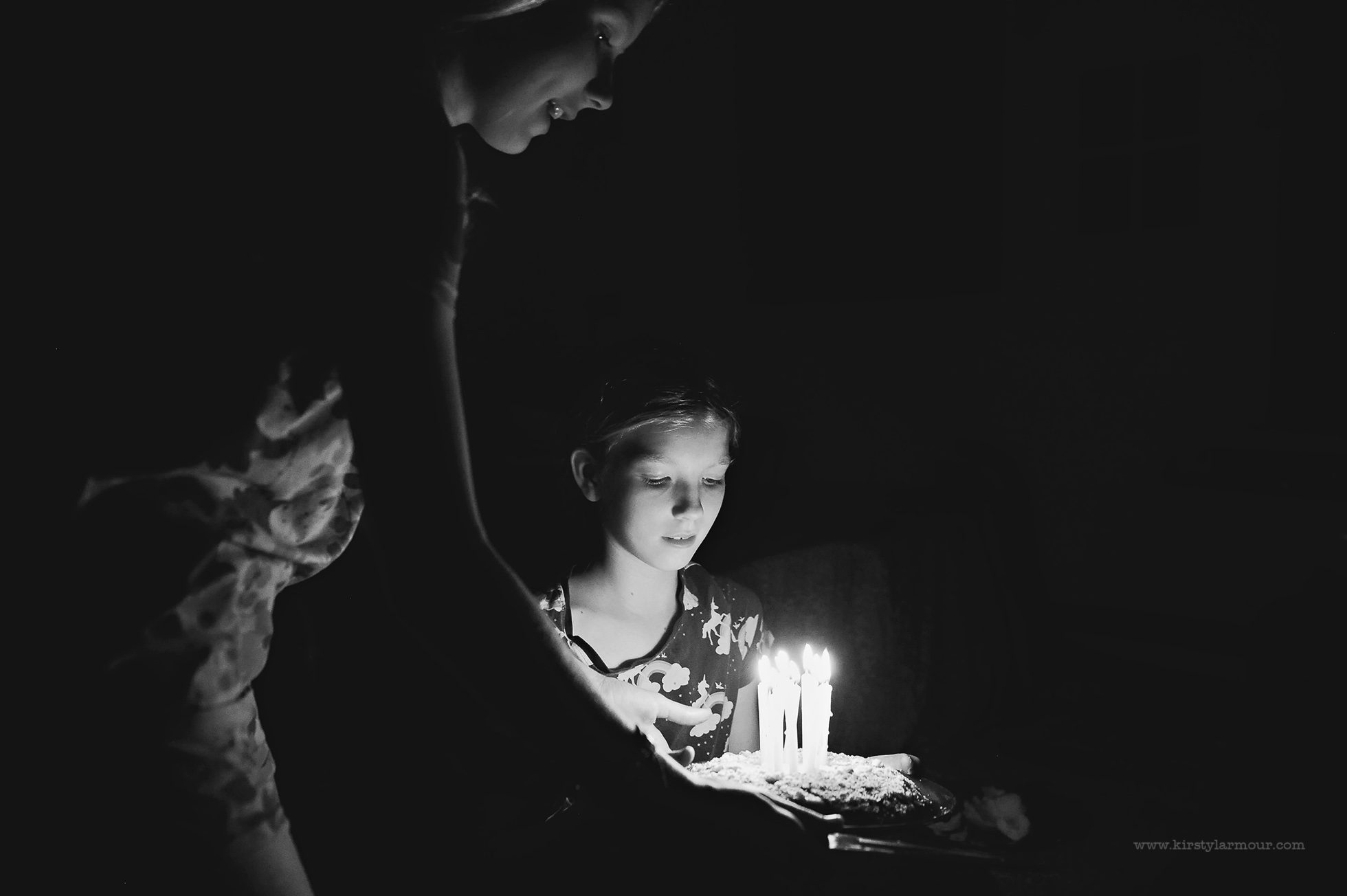 An older girl gives her younger sister a birthday cake with 11 candles | by Kirsty Larmour
