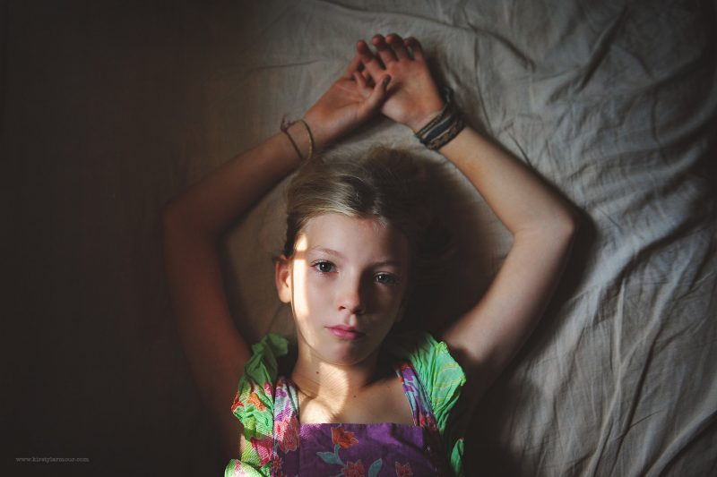 A girl lays in a patch of light | Kirsty Larmour