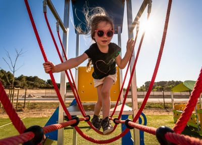 Child playing on colorful rope climbing frame at playground with sunburst and backlight