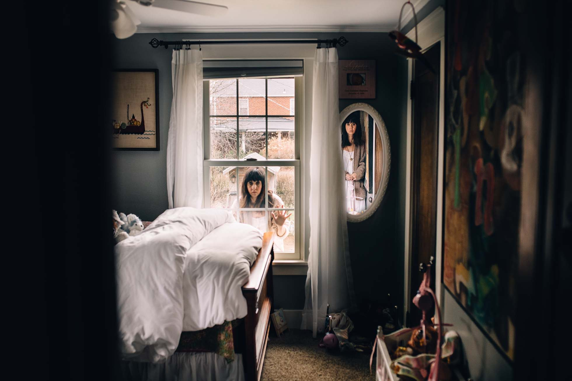 woman looking through the window of her child's room while observing her reflection in the mirror
