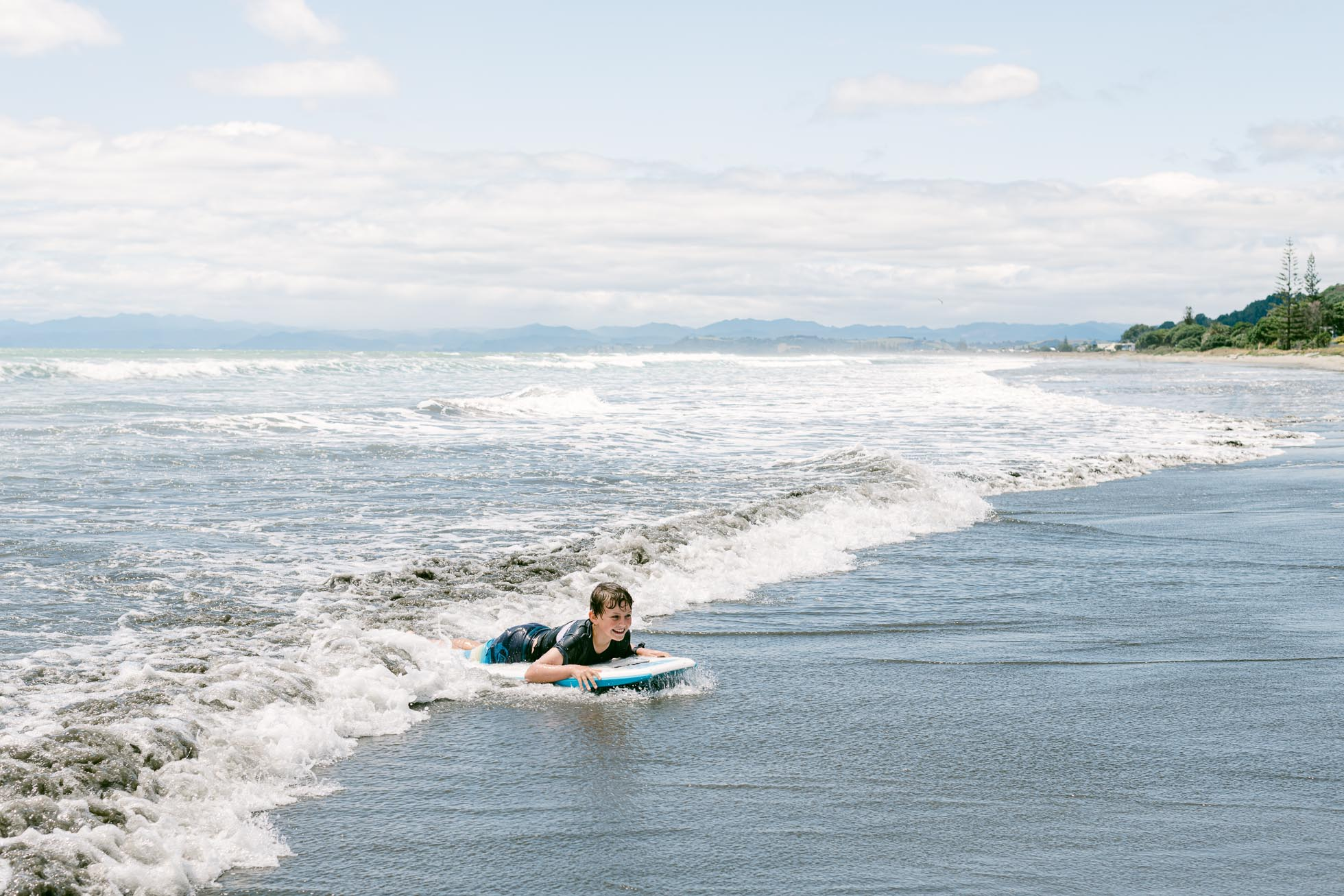 boy boogie boarding at Ohope Beach, New Zealand