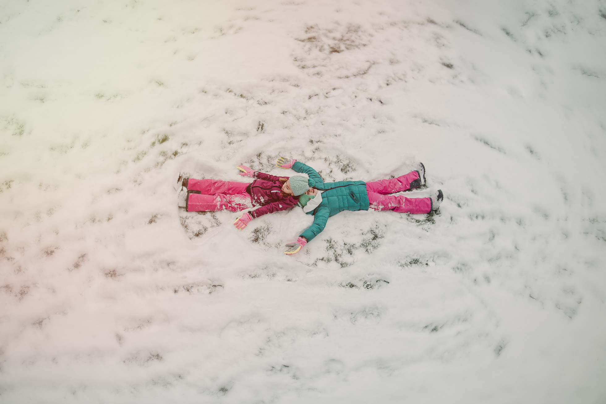 girls play in snow making snow angels