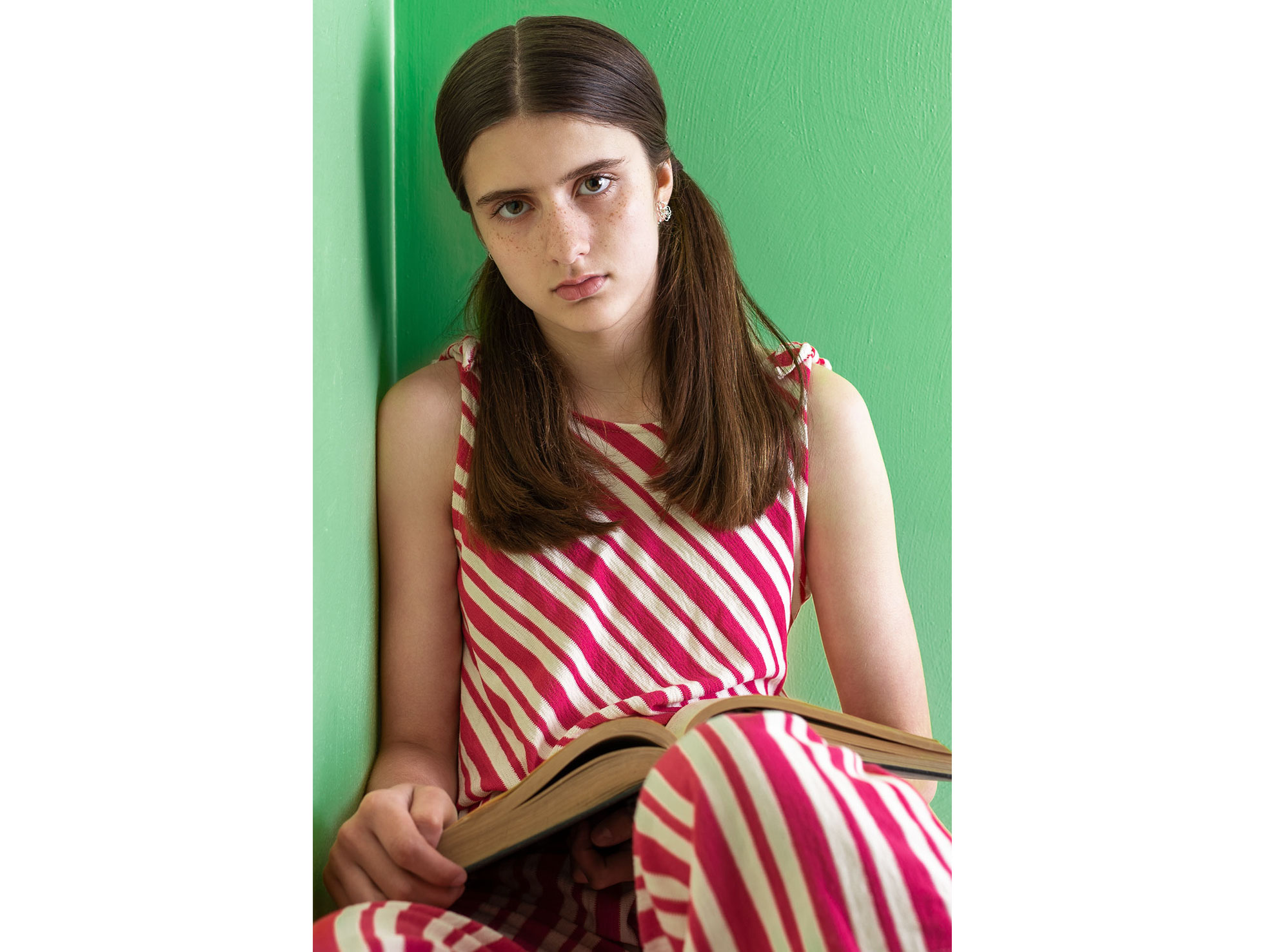 Portrait of a teenage girl with a book in her lap. Dressed in a pink-striped jumpsuit to contrast with the green wall she leans against.